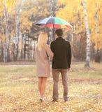 与伞一起的愉快的年轻夫妇在秋天停放 免版税库存照片