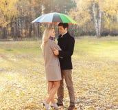 与伞一起的年轻夫妇在秋天 库存照片