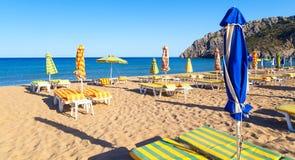 与伞和sunbeds,夜的Tsampika海滩离开了,罗得岛,希腊 免版税图库摄影