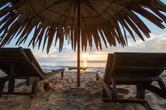 与伞在海滩,日出的太阳懒人 免版税库存照片