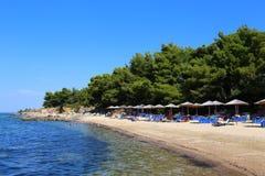 与伞的具球果海滩在Halkidiki, Sithonia 免版税库存图片