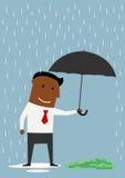 与伞的商人保护的金钱 库存照片