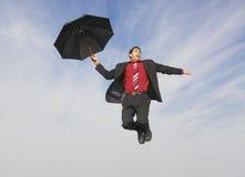 与伞的商人飞行反对多云天空 免版税库存照片
