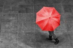 与伞的女孩步行在路面艺术性的转换的雨中 免版税图库摄影