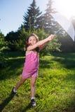 与伞的愉快的女孩跳舞在夏天太阳 免版税库存照片