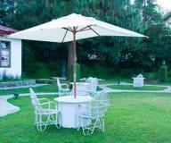 与伞的椅子在庭院里 免版税库存照片
