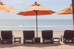 与伞的海滩睡椅在洋锋 库存照片