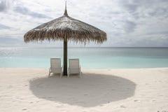 与伞的海滩睡椅在一个多云晴天 免版税库存图片