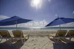 与伞的海滩睡椅在阳光下在海滩 免版税库存图片