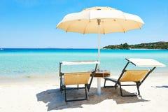 与伞的海滩睡椅 免版税库存照片