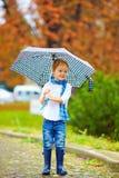 与伞的逗人喜爱的孩子在公园,多雨天气 免版税库存照片
