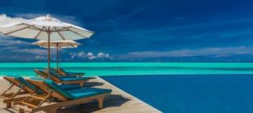 与伞的轻便折叠躺椅在马尔代夫依靠与无限水池 库存照片