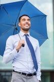 与伞的年轻微笑的商人户外 免版税图库摄影