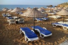与伞的Sunbeds在沙子海滩 库存图片