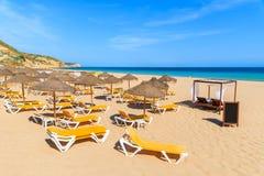 与伞的Sunbeds在沙滩 免版税库存照片