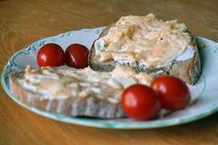 与传播的健康早晨早餐在面包和西红柿在板材 库存照片