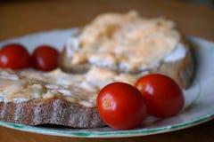 与传播的健康早晨早餐在面包和西红柿在板材 免版税库存图片