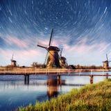 与传统荷兰风车运河的五颜六色的春天夜在鹿特丹 在湖岸附近的木码头 荷兰 免版税图库摄影