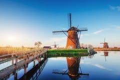 与传统荷兰风车运河的五颜六色的春日在鹿特丹 在湖岸附近的木码头 荷兰 免版税库存照片