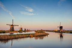 与传统荷兰风车运河的五颜六色的春日在鹿特丹 在湖岸附近的木码头 荷兰 库存图片