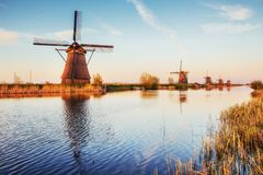 与传统荷兰风车运河的五颜六色的春日在鹿特丹 在湖岸附近的木码头 荷兰 库存照片