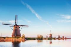 与传统荷兰风车运河的五颜六色的春日在鹿特丹 在湖岸附近的木码头 荷兰 免版税库存图片