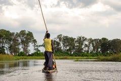 与传统mokoro小船的独木舟旅行在河通过在马翁,博茨瓦纳非洲附近的Okavango三角洲 免版税库存图片