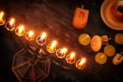 与传统spinnig上面、menorah & x28的犹太假日光明节背景; 传统candelabra& x29;并且燃烧的蜡烛 免版税库存照片