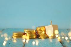 与传统spinnig上面和巧克力硬币的犹太假日光明节图象背景 库存照片