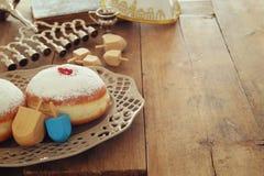 与传统spinnig上面的犹太假日光明节背景、多福饼和menorah & x28; 传统candelabra& x29;