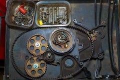 与传送带和齿轮的汽车修理在难看的东西桌里 库存照片