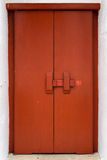 与传统横臂锁的红色木门 免版税库存图片