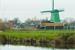 与传统荷兰风车和老农厂房子的农村风景河岸的 免版税库存照片