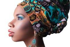 与传统非洲样式的年轻美好的时装模特儿与围巾、耳环和构成在橙色背景 免版税库存照片