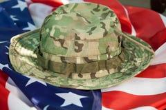 与伪装作战帽子的美国旗子 免版税库存图片