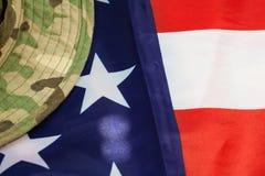 与伪装作战帽子的美国旗子 图库摄影