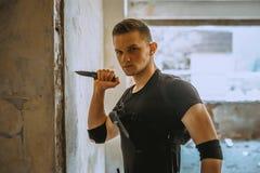 与伪装的男性特别solider做与刀子的自卫锻炼 免版税库存图片