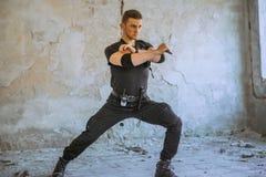 与伪装的男性特别solider做与刀子的自卫锻炼 图库摄影