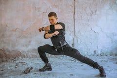 与伪装的男性特别solider做与刀子的自卫锻炼 免版税图库摄影
