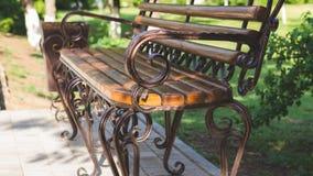 与伪造在游乐场的金属艺术的长木凳 在自然绿色背景的布朗长凳  库存图片