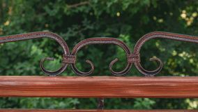 与伪造在游乐场的金属艺术的长木凳 在自然绿色背景的布朗长凳  图库摄影