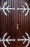 与伪造的铰链的老棕色木门 库存图片