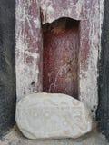 与佛教佛经的石头在梵语在西藏修道院的墙壁附近 图库摄影