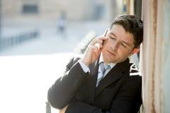 与佩带在手机的闭合的眼睛的年轻可爱和繁忙的商人衣服和领带谈的事务户外 图库摄影