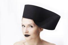 与佩带大时髦的设计师黑色独特的帽子戴头受话器的蓝眼睛和黑唇膏的华美的白肤金发的妇女模型 免版税库存照片