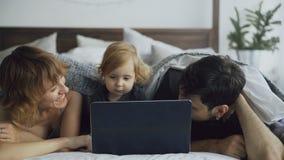 与使用与女儿的逗人喜爱的小女孩的年轻家庭,当她在家时在床上的观看的便携式计算机 库存照片