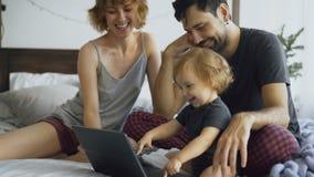 与使用与女儿的逗人喜爱的小女孩的年轻家庭,当键入在便携式计算机上的她在家时坐在床上 库存图片