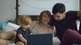 与使用与女儿的逗人喜爱的小女孩的年轻家庭,当键入在便携式计算机上的她在家时坐在床上 免版税库存图片