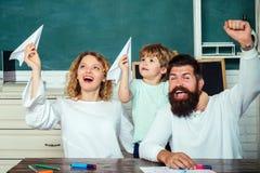 与使用与父母的纸飞机的学生 家庭学校 小男孩和他的父母好的全家福  ?? 免版税库存图片