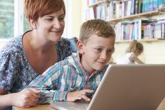 与使用便携式计算机的老师的学校学生在教室 免版税图库摄影